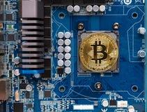 Goud bitcoin op motherboard stock foto's