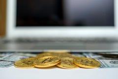 Goud bitcoins en dollarrekeningen die van boven laptop met beursgrafieken verschijnen op het scherm royalty-vrije stock foto