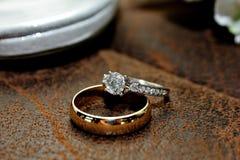 Goud en Diamond Wedding Ring op Leeroppervlakte stock fotografie