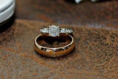 Goud en Diamond Wedding Ring op Leeroppervlakte stock afbeelding