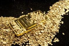 Goud in muntstukken, goudklompjes en baren Stock Fotografie