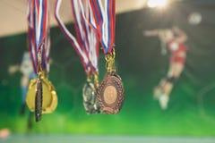 Goud, zilver en bronsmedaille op achtergrond van affiche met volleyballspelers stock afbeelding