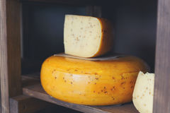 Gouda cheese as wheel and piece on wooden shelf of a grocery sho. Gouda pesto cheese as wheel and piece on grocery shop wooden shelf, closeup royalty free stock photography