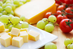 Cheese snack. Gouda cheese snack with grapes and tomatoes Royalty Free Stock Photo