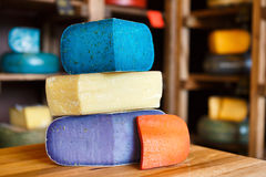 Gouda pesto cheese assortment. Lavender, blue, violet and red at grocery shop background Stock Photos