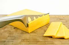 Gouda Sliced. Slicing Gouda with a cheese knife on a wooden board Royalty Free Stock Photo