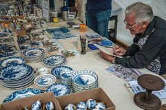 Skilled artisan hand-painting crockery in the region typical style at Gouda. royalty free stock images