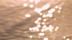 Gouden achtergrond van gegolfte waterspiegel, vaag beeld stock footage