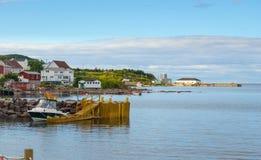 Gouden adirondackstoelen op een rotspier Huizen op het overzees langs een dorpsoever Royalty-vrije Stock Fotografie