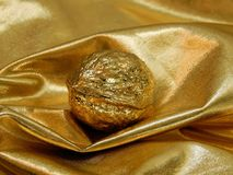 Gouden bar met een noot van bladgoud op een gouden achtergrond Royalty-vrije Stock Afbeeldingen