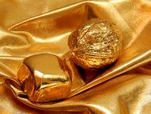 Gouden bar met een noot van bladgoud op een gouden achtergrond Royalty-vrije Stock Foto's