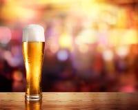 Gouden Bier in Glas met Lichten van Bar Royalty-vrije Stock Afbeeldingen