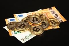 Gouden bitcoin fysieke muntstukken op document Euro bankbiljet stock fotografie
