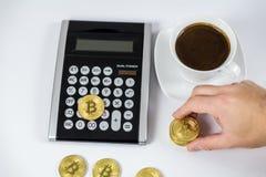 Gouden Bitcoin hield met de hand op zwarte calculator naast koffie, cryptocurrencyconcept royalty-vrije stock foto