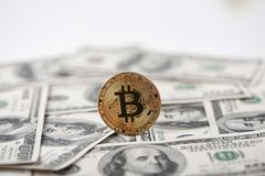 Gouden bitcoin met honderd dollarsbankbiljetten op achtergrond stock foto's