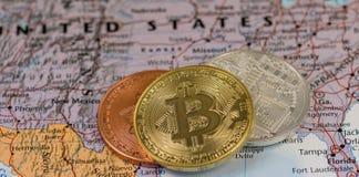 Gouden Bitcoin-Muntstuk dichte omhooggaand samen met zilveren bitcoin en brons bitcoin met vage achtergrond van Verenigde Staten stock afbeeldingen