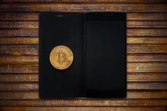 Gouden bitcoincryptocurrency met een smartphone Stock Afbeelding