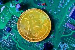 Gouden bitcoinmedaille op mainboard stock fotografie