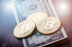 Gouden bitcoinmuntstukken op een document dollarsgeld en een donkere achtergrond met zon Virtuele munt Crypto munt nieuw virtueel Royalty-vrije Stock Afbeelding