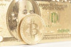 Gouden bitcoinmuntstukken op ons dollars Royalty-vrije Stock Foto's