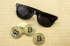 Gouden bitcoins op bureau, cryptocurrencyachtergrond met zonnebril stock foto
