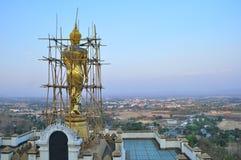 Gouden boeddhistisch beeldhouwwerk onder vernieuwingsvooruitgang bovenop heuvel Royalty-vrije Stock Foto