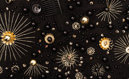 Gouden borduurwerk van bloemen en zwarte parels op stof stock afbeelding