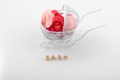 Gouden brieven en kinderwagenhoogtepunt van bloemen op witte achtergrond Word baby op wit Pasgeboren groetkaart Stock Foto's