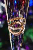 Gouden bruiloftringen in glas champagne met bellen op kleurrijke heldere achtergrond Stock Foto