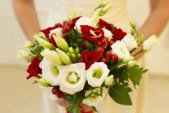 Gouden bruiloftringen onder rode bessen en witte en rode rozen en groene knoppen van huwelijksboeket Stock Foto's