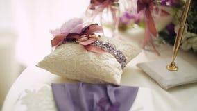 Gouden bruiloftringen op klein wit kussen stock videobeelden