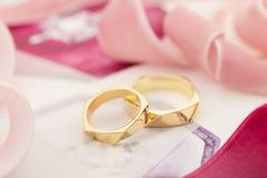 Gouden bruiloftringen op pastelkleurachtergrond met roze linten Stock Afbeelding
