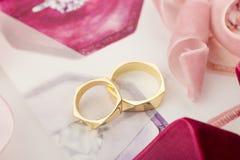 Gouden bruiloftringen op pastelkleurachtergrond met roze linten Stock Foto's