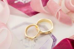 Gouden bruiloftringen op pastelkleurachtergrond met roze linten Stock Afbeeldingen