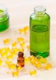 Gouden capsules van natuurlijke cosmetik voor gezicht en flessen met etherische oliën op de houten achtergrond Stock Foto