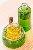Gouden capsules van natuurlijke cosmetik voor gezicht en flessen met etherische oliënclose-up Stock Afbeelding