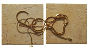 Gouden chainlets liggen op steen royalty-vrije stock afbeeldingen
