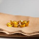 Gouden Chinese baar (Yuan Bao) plaats op jute Royalty-vrije Stock Afbeelding