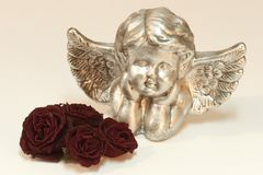 Gouden cupid met rozen stock foto's