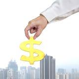 Gouden 3D het geldsymbool van de handgreep met stadsmening Stock Foto