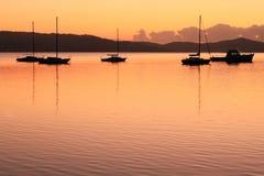 Gouden dageraad over meer met vijf boten royalty-vrije stock foto's