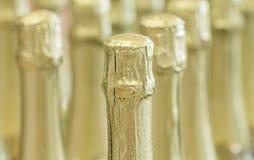 Gouden de flessenhalzen van Champagne en hoogste kappen bij de status van de lichte achtergrond in voorraad Stock Afbeeldingen