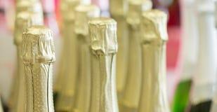 Gouden de flessenhalzen van Champagne en hoogste kappen bij de status van de lichte achtergrond in voorraad Stock Foto's