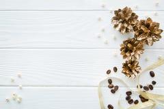 Gouden denneappels, beige parels en gouden lint op witte houten stock afbeeldingen