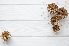 Gouden denneappels en beige parels op witte houten lijstbackgrou stock afbeelding