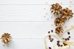 Gouden denneappels en gouden lint op witte houten lijst backgr stock foto's