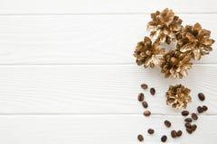Gouden denneappels op witte houten lijst De decoratie van koffiebonen royalty-vrije stock afbeeldingen