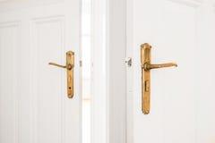 Gouden deurhandvat op oude witte deuren Stock Afbeeldingen