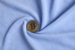 Gouden die bitcoin ligt op een deken van zachte en pluizige lichtblauwe vachtstof wordt gemaakt met een groot aantal hulpvouwen S stock fotografie