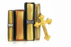 Gouden die kruis tegen gouden boeken wordt geleund Stock Foto